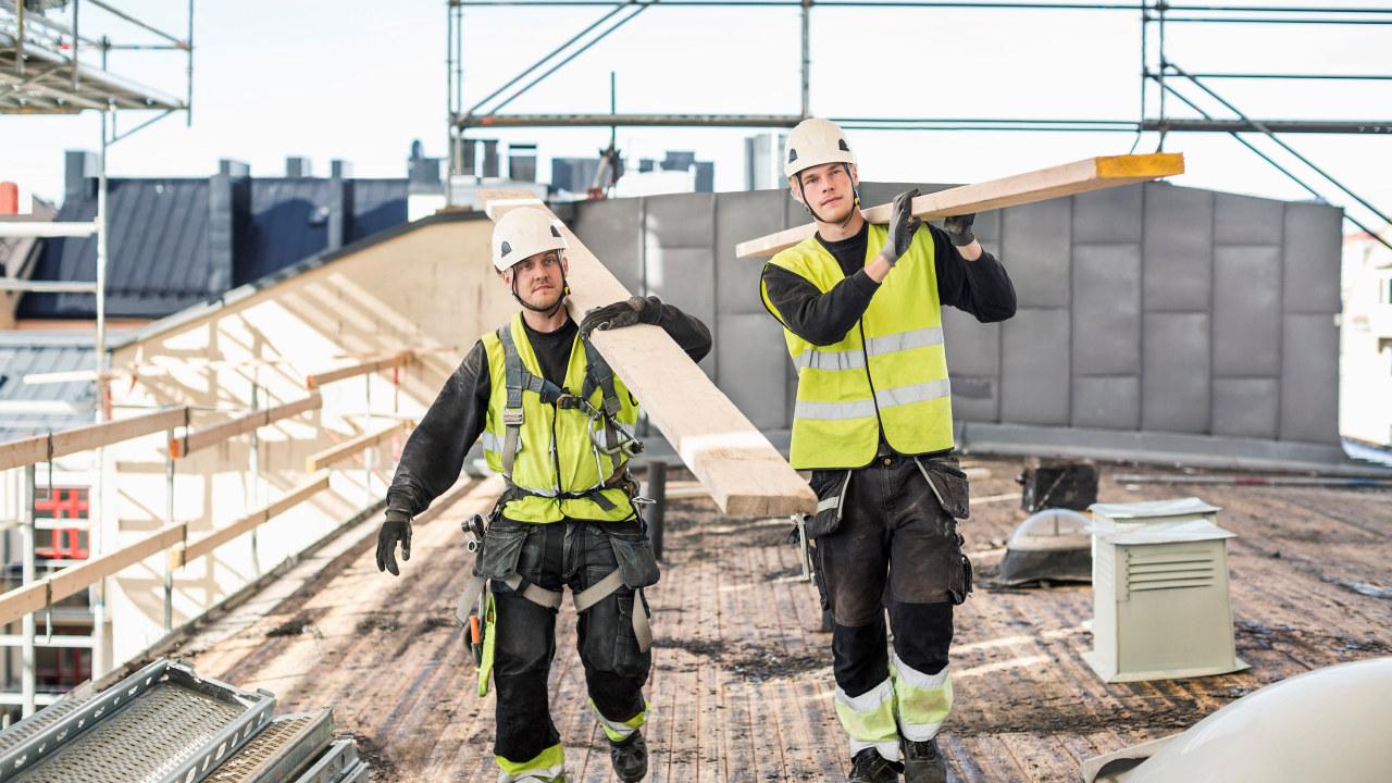 To menn som bærer trebjelker på en arbeidsplass.