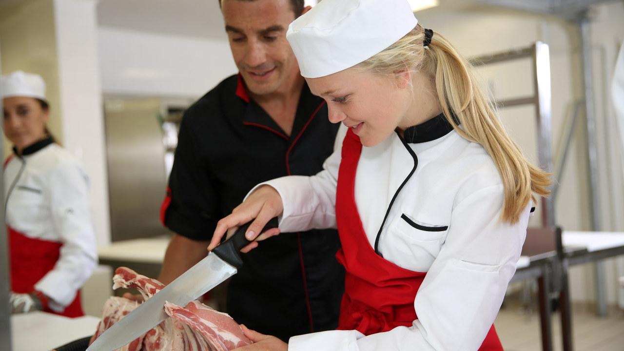 En jente lærer å skjære kjøtt