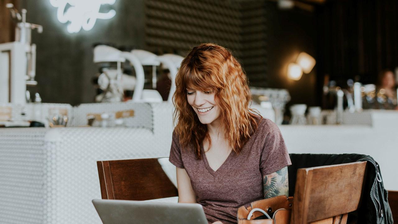 Ung kvinne som sitter på datamaskin.