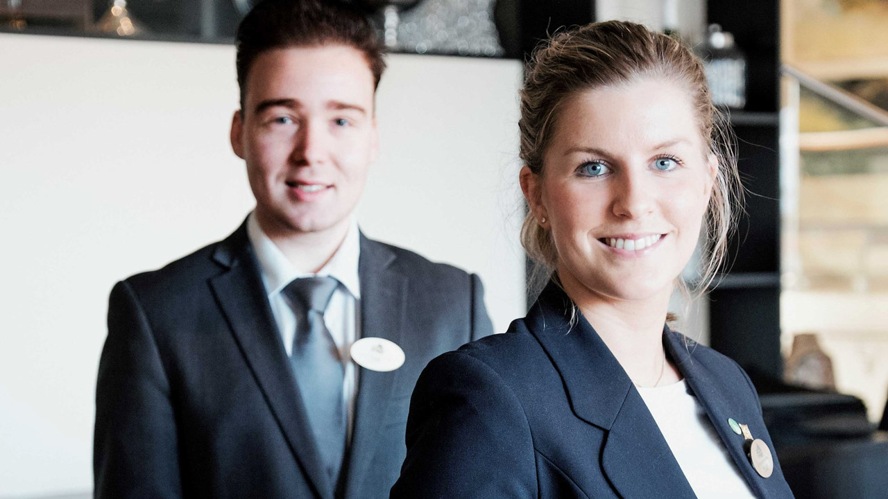 To hotellansatte som står bak resepsjonen og smiler