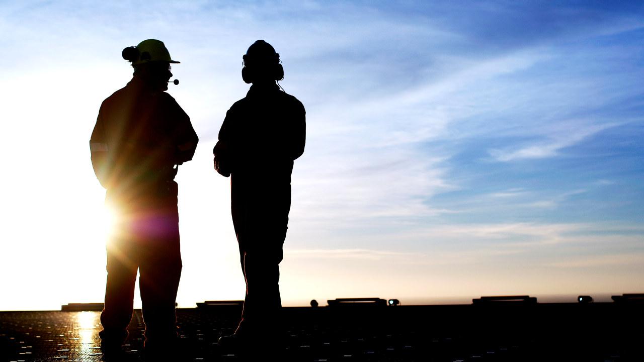 Illustrasjonsfoto: To menn i verneklær på en oljeplattform.