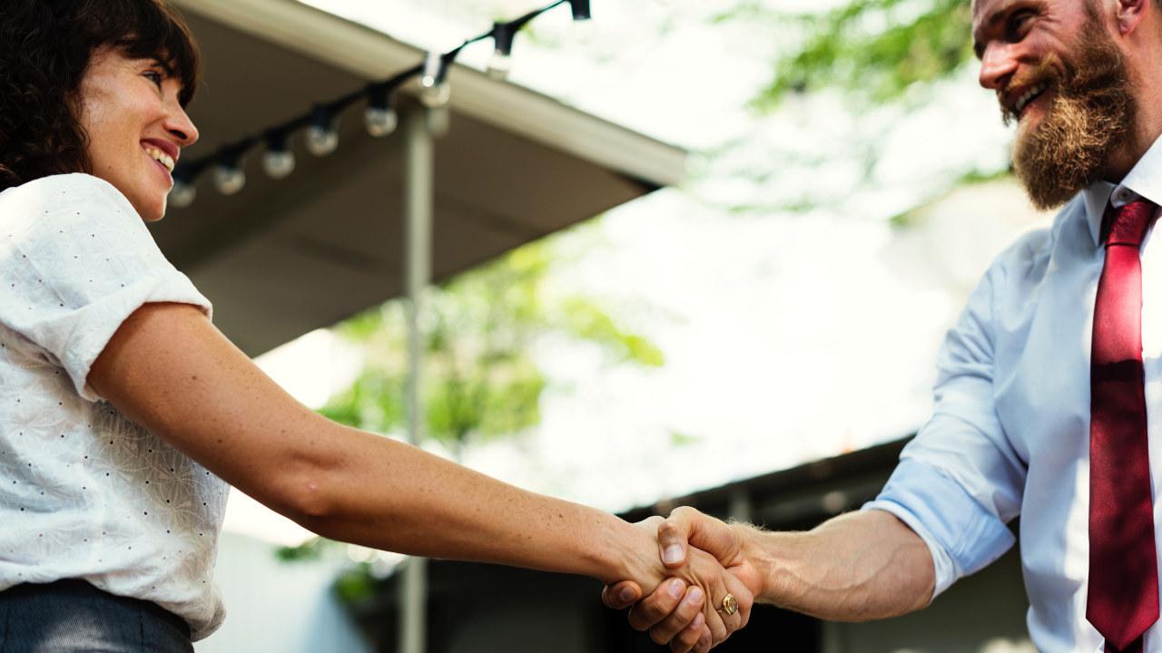 En smilende mann og kvinne som håndhilser.