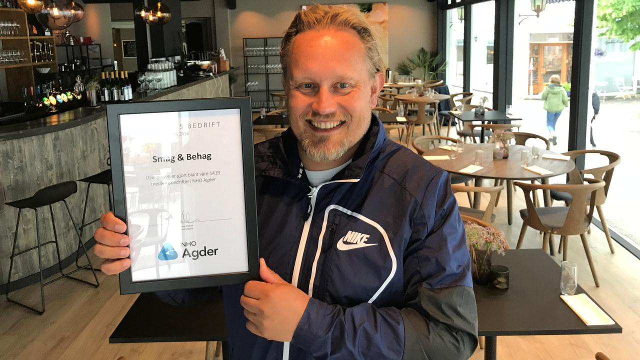 Hans Petter Klemmetsen holder opp diplomet som viser at Smag & Behag er kåret som Månedens bedrift i juli 2018 av NHO Agder.