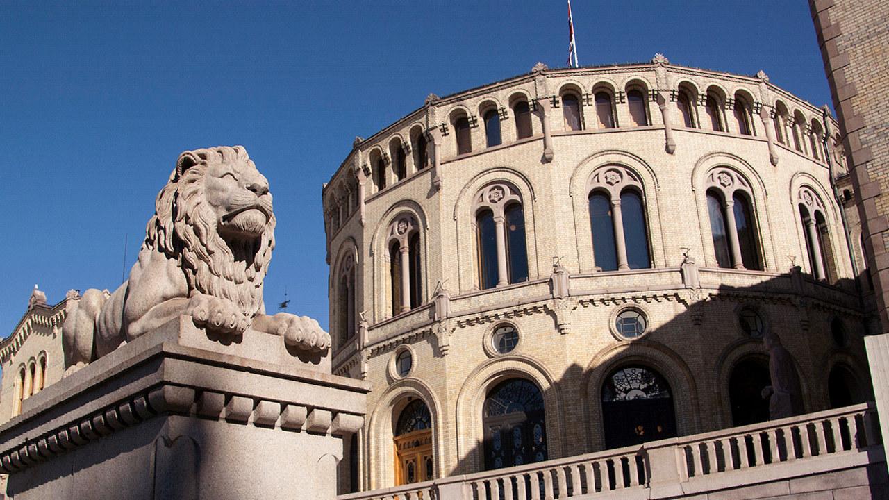 Bilde av Stortinget, med en av løvene i forgrunnen