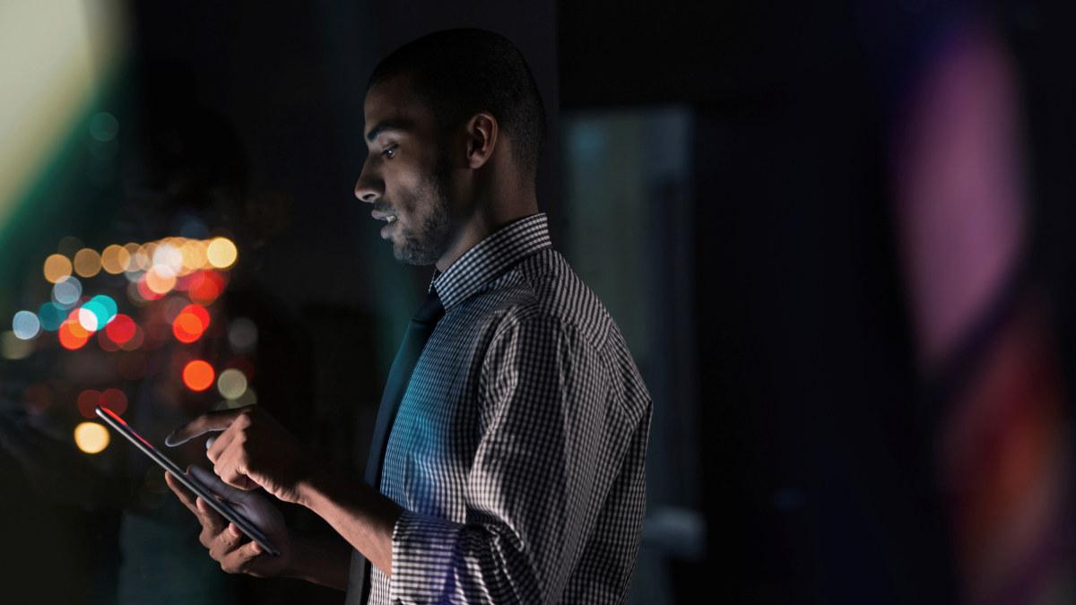 En ung mann bruker sitt nettbrett på jobben sent på kvelden.