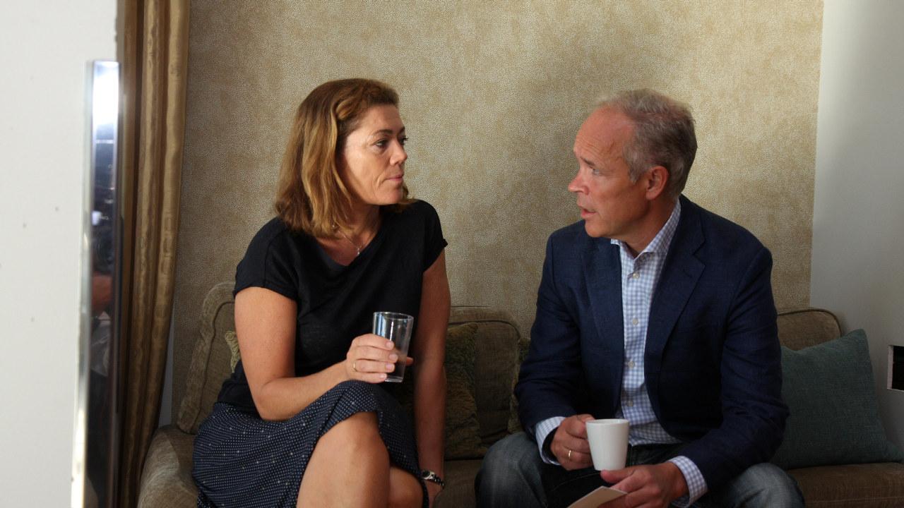 Kristin Skogen Lund og Jan Tore Sanner sitter og snakker sammen.