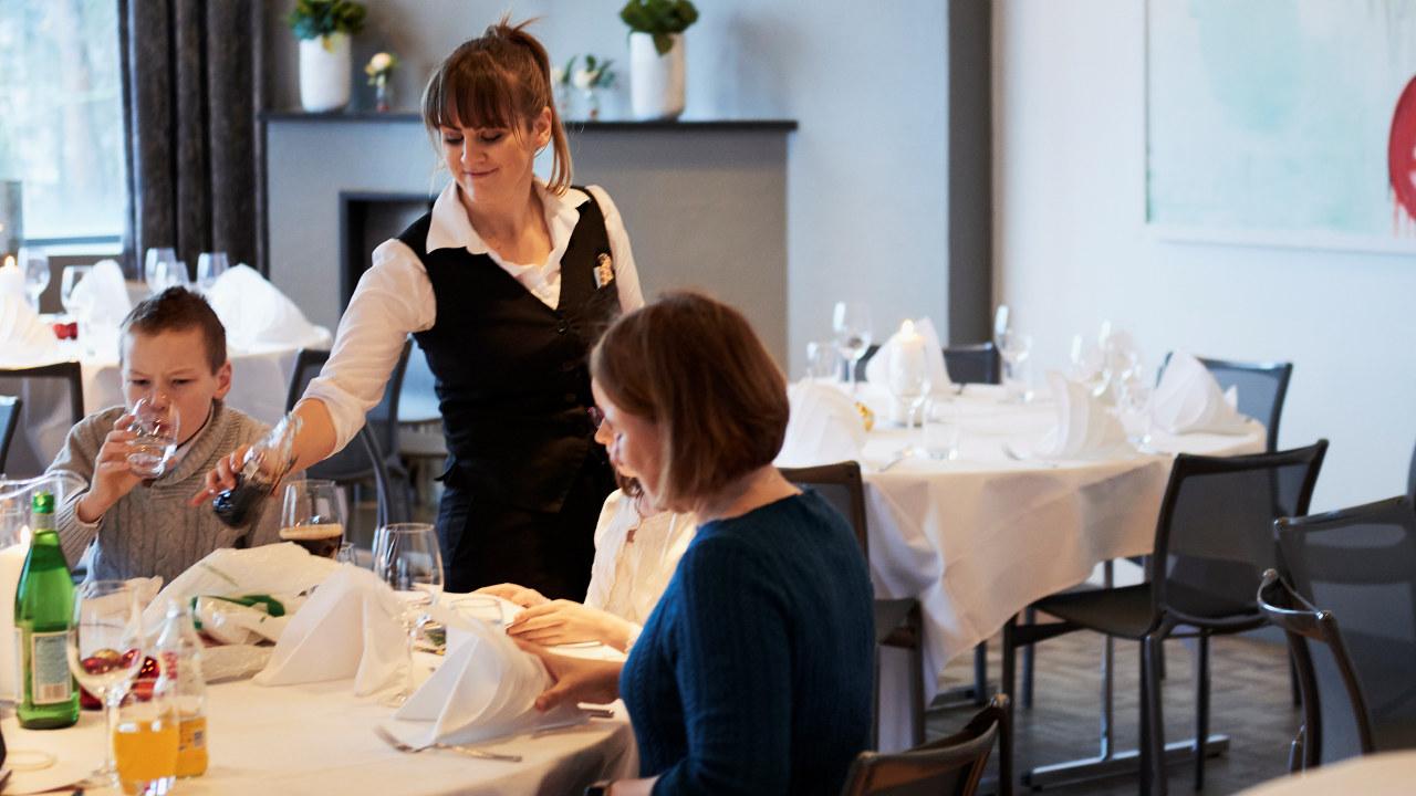 Servitør serverer drikke på Ekebergrestauranten.