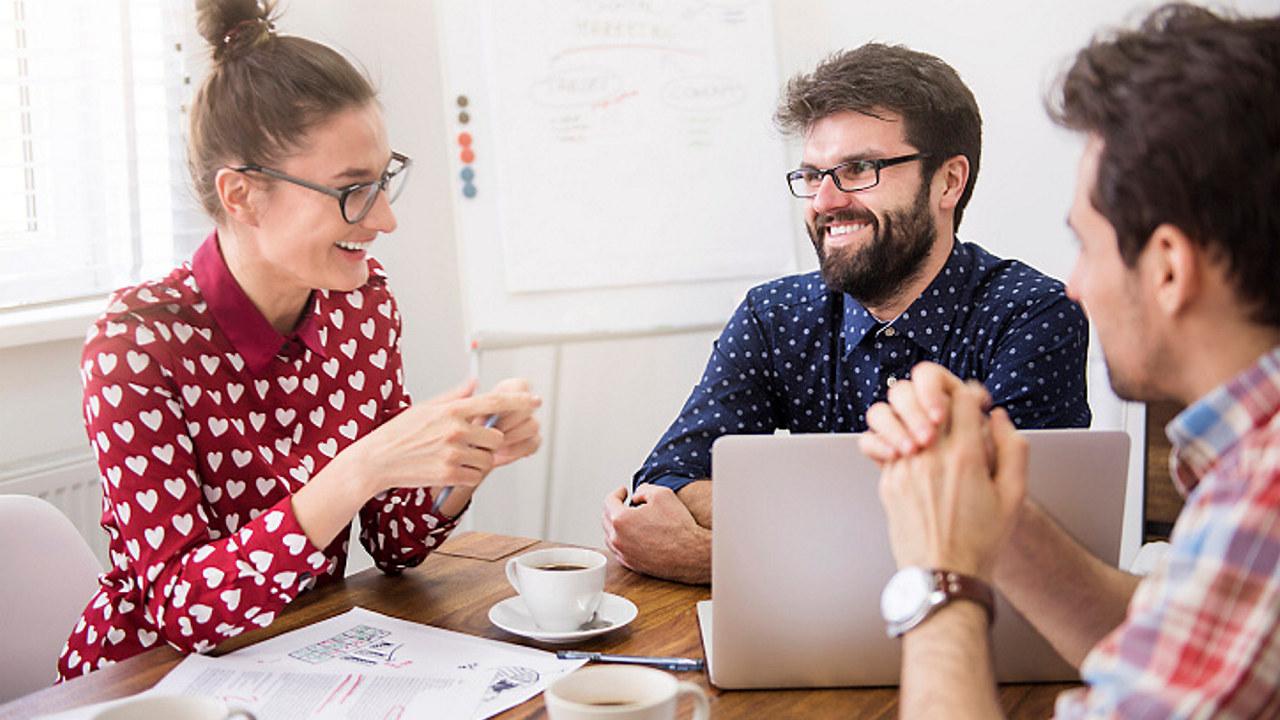 Dame og to menn som sitter ved arbeidsbord og snakker