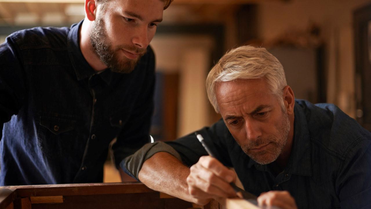 Mann veileder yngre mann i snekkerarbeid.