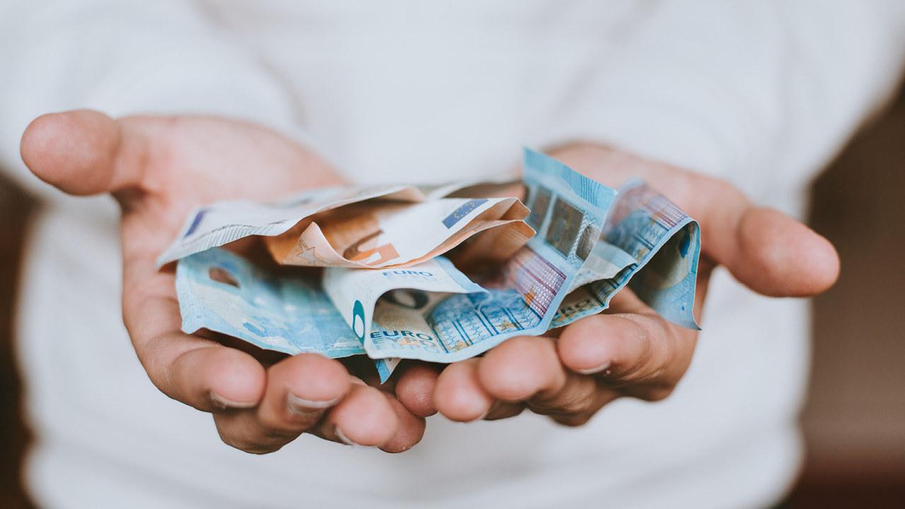 Person med pengesedler i hånda