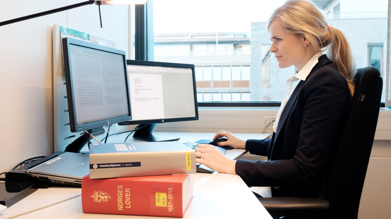 Dame som sitter og jobber på en datamaskin.