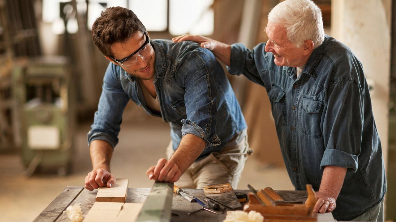 Eldre mann klapper yngre mann på skulderen. Foto.