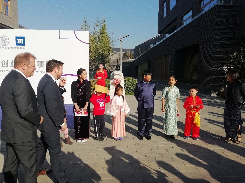 Rektor Inge Jan Henjesand og næringsminister Torbjørn Røe Isaken ble ønsket velkommen av kinesiske barn før seremonien der Handelshøyskolen BI inngikk samarbeid med Tsinghuauniversitetet.