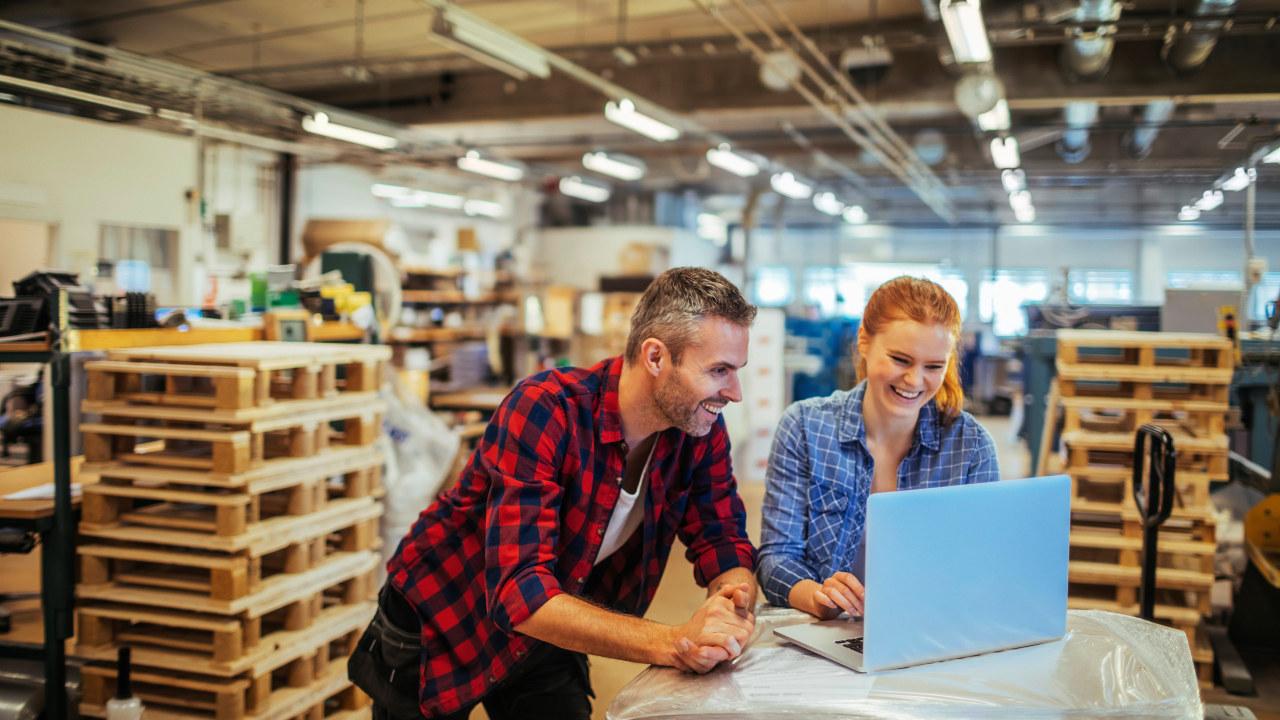 En kvinne og en mann som ser på en laptop.