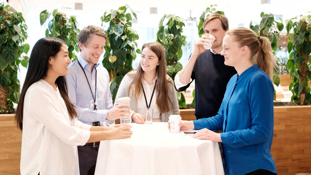 Fem personer står rundt et bord.