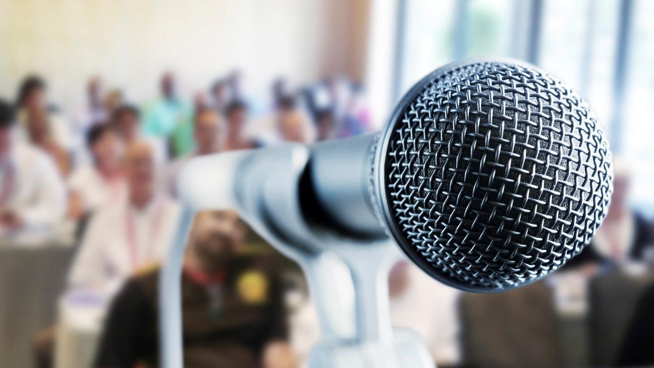 Nærbilde av mikrofon, publikum i bakgrunn. Foto.