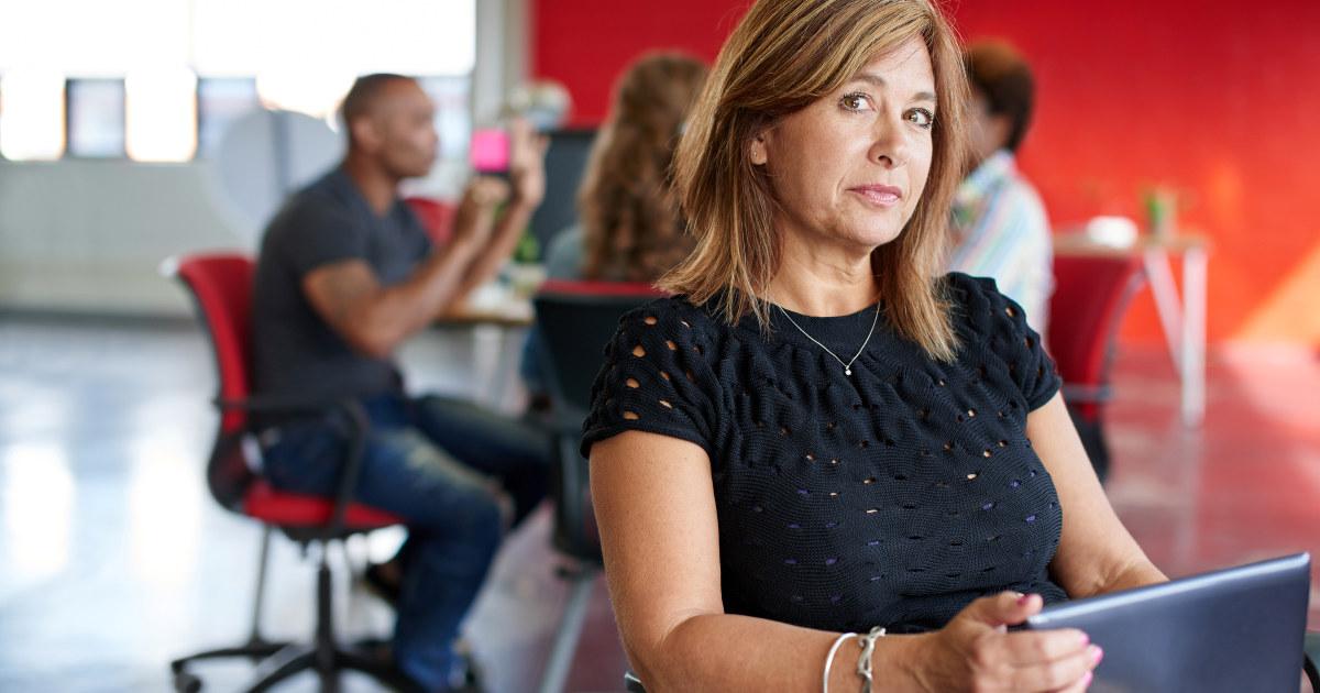Kvinnelig sjef i 40-årene ser i kamera. Ansatte prater i bakgrunnen.