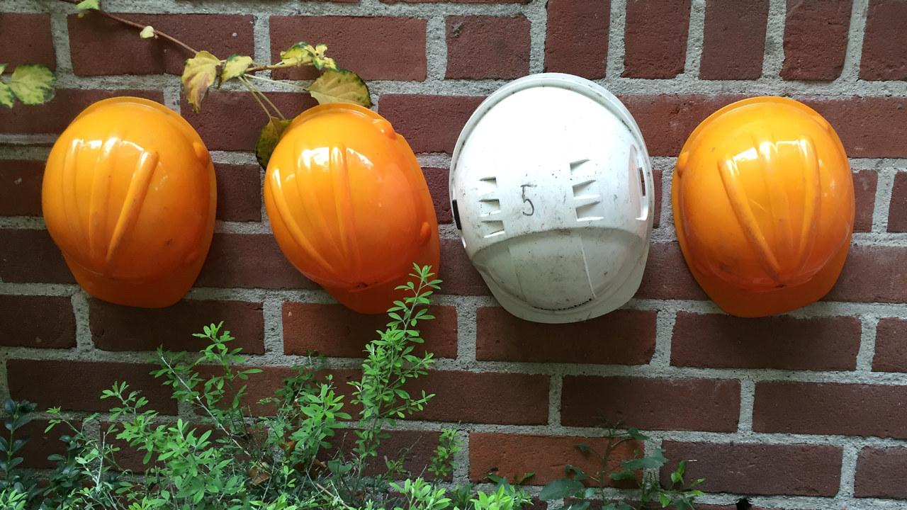 Fire hjelmer som henger på en murvegg