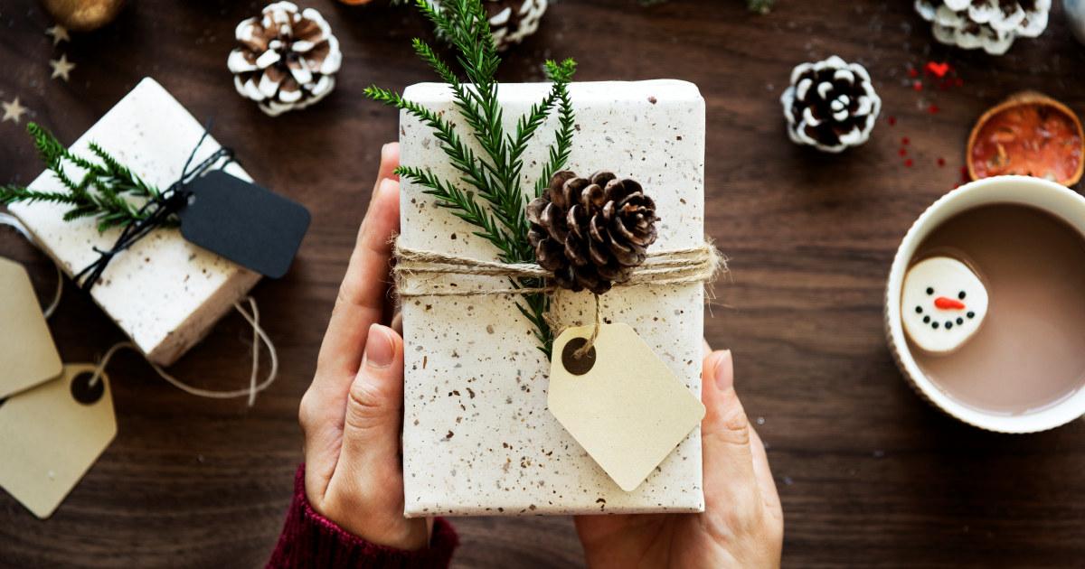 To hender holder en gave som er innpakket.