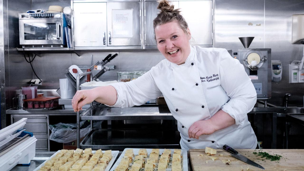 Kokk på Hurtigruten smiler. Hun lager frokost.