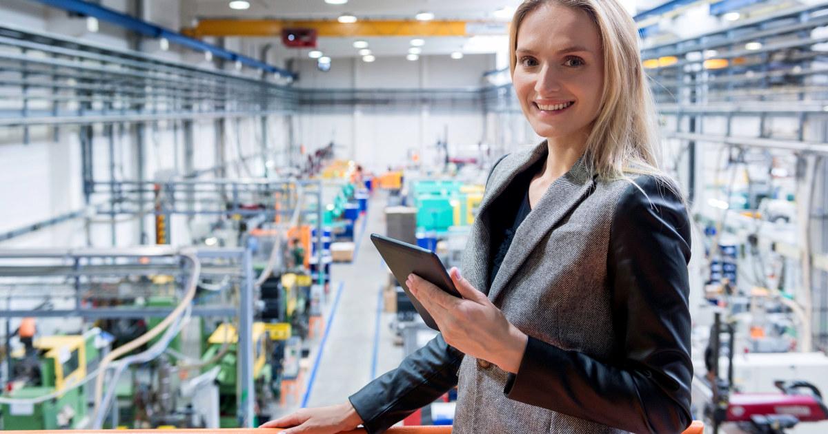 Kvinne med skjermbrett i et industrilokale.