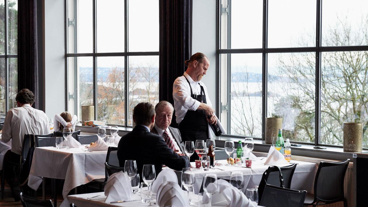 Servitør serverer to menn på Ekebergrestauranten