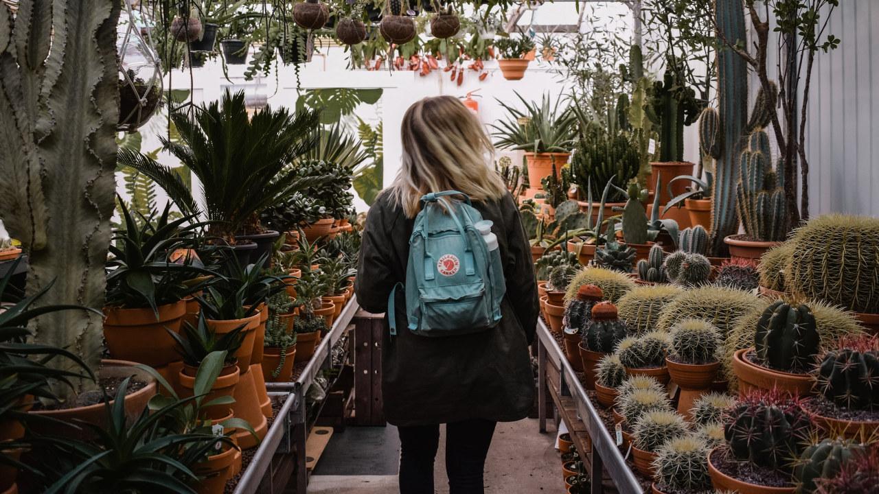 Jente med ryggsekk på gartneri