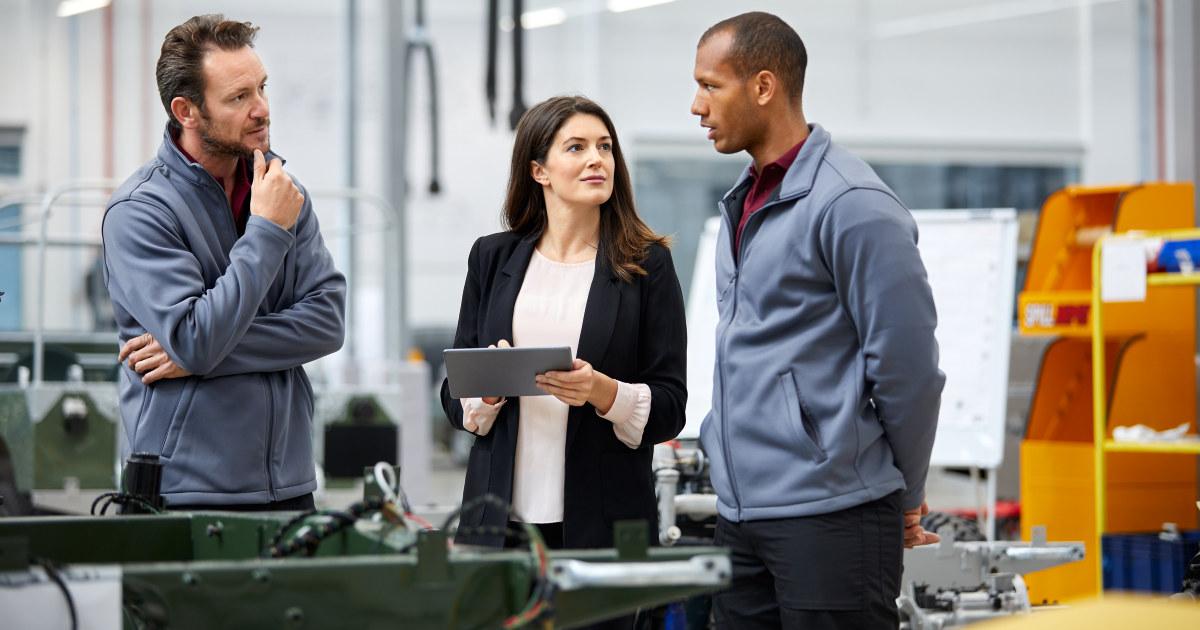 Kvinne snakker med to ansatte i en bilfabrikk