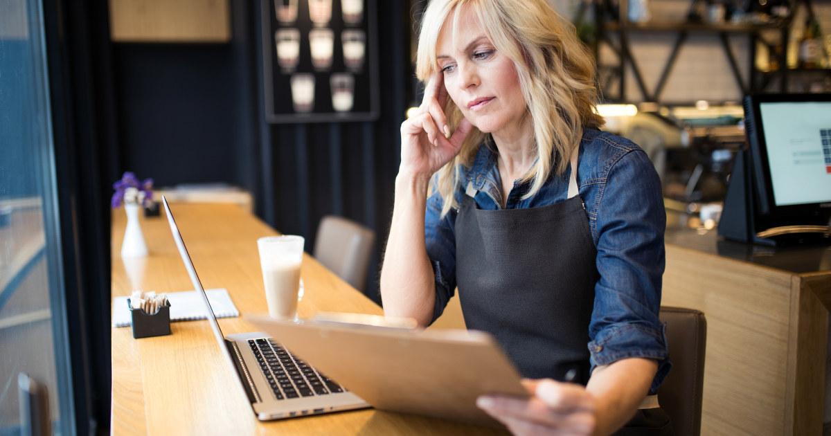 Kvinne i 40-årene på jobb som tenker foran sin bærbare datamaskin.