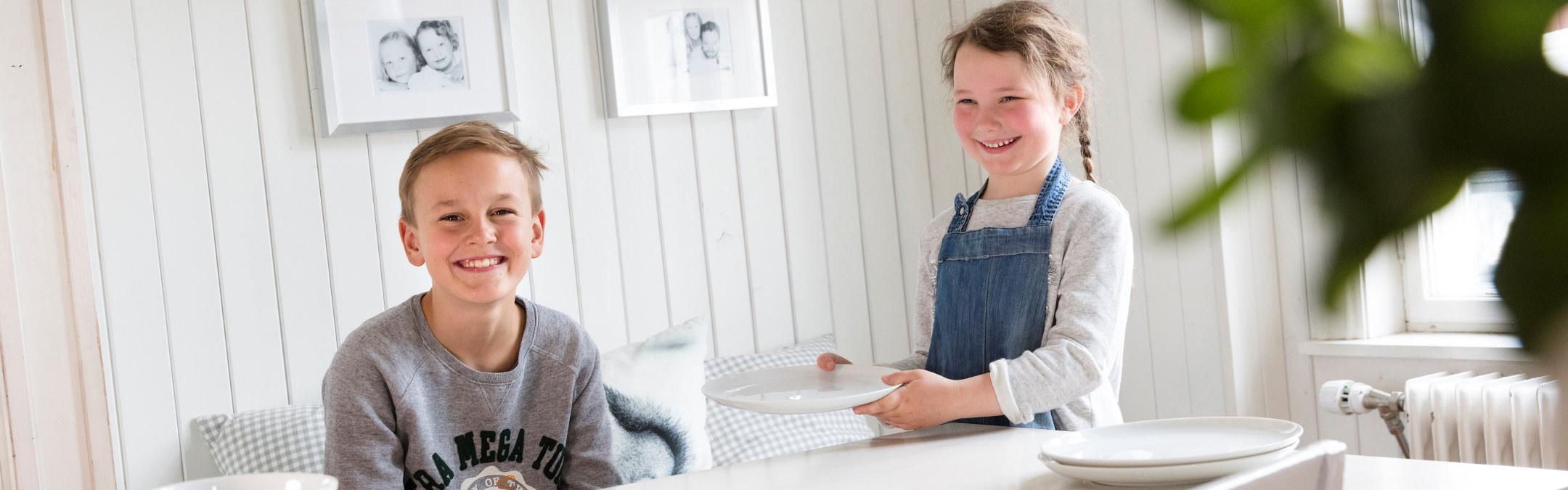 Barn som dekker på til middag på kjøkkenet