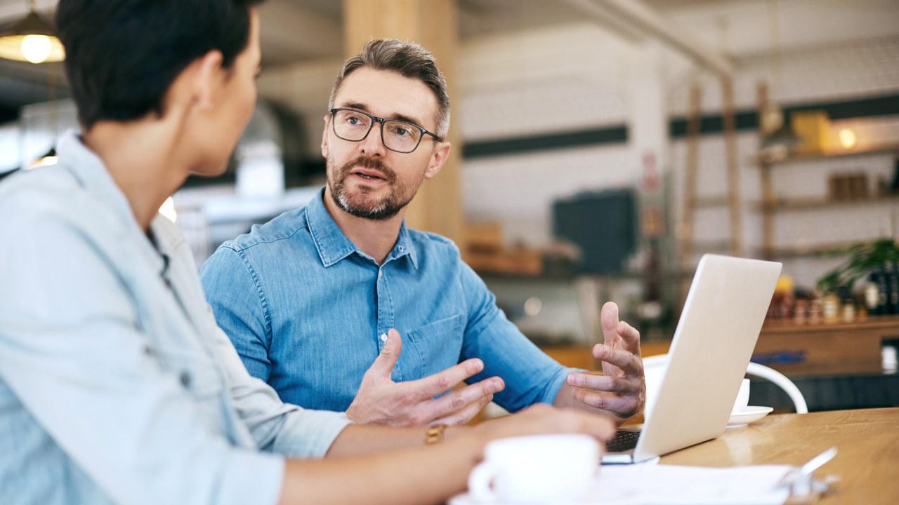 Mann med dongeriskjorte og briller sitter og snakker med en kollega. Mannen som snakker har en PC foran seg.