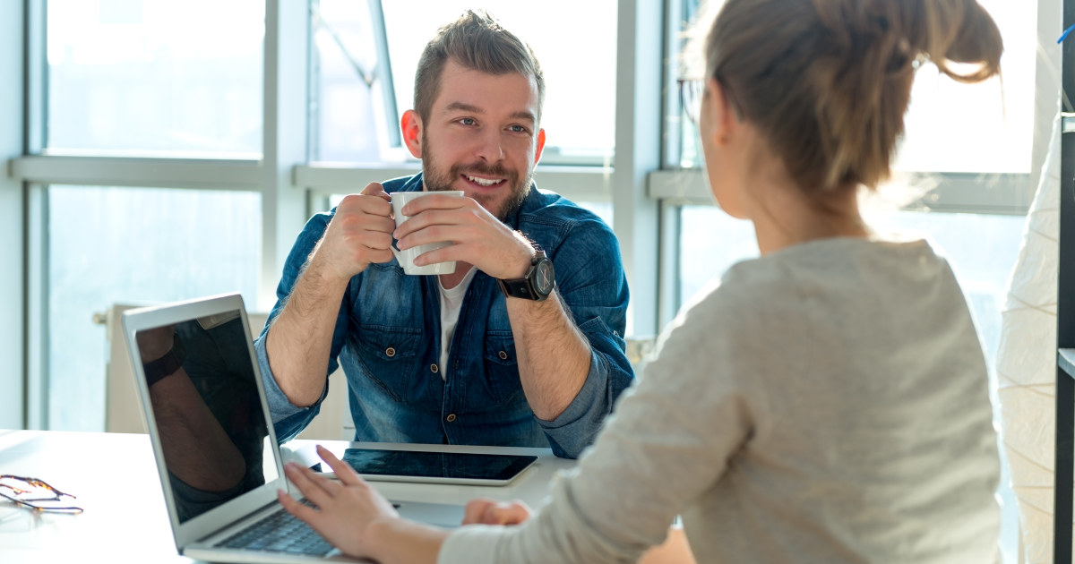 Kvinne med PC og ryggen til snakker til mann som drikker kaffe.