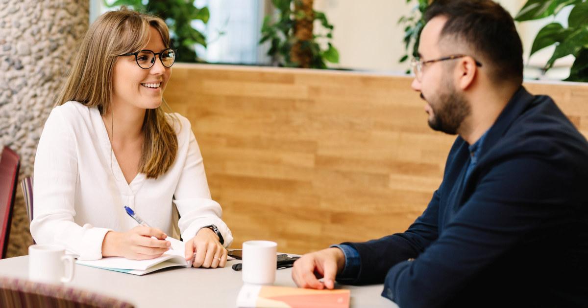 En kvinne og en mann snakker sammen på jobb.