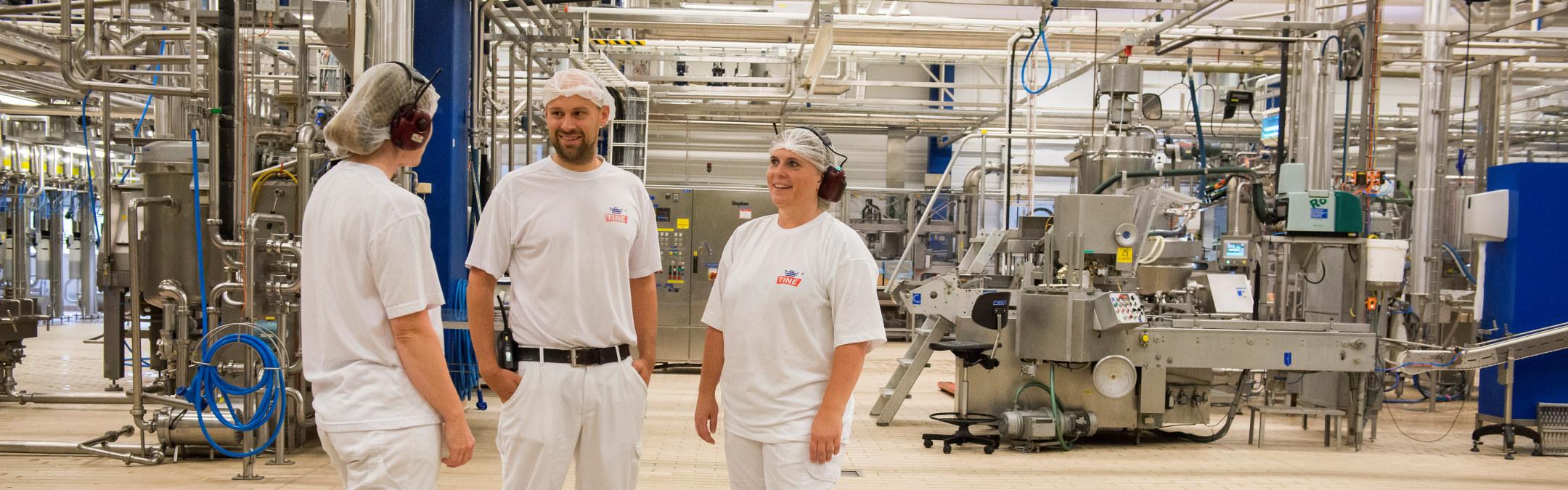 Tre ansatte hos TINE i deres produksjonslokale