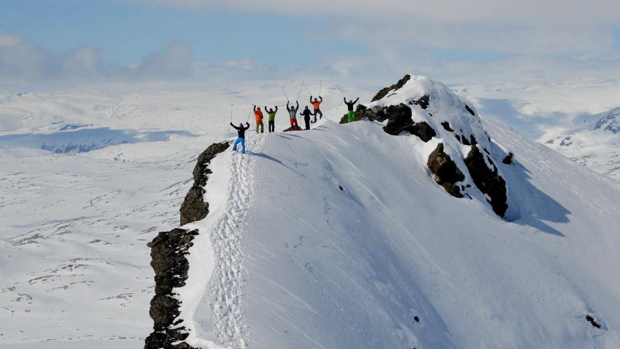 Syv personer på toppen av en tind