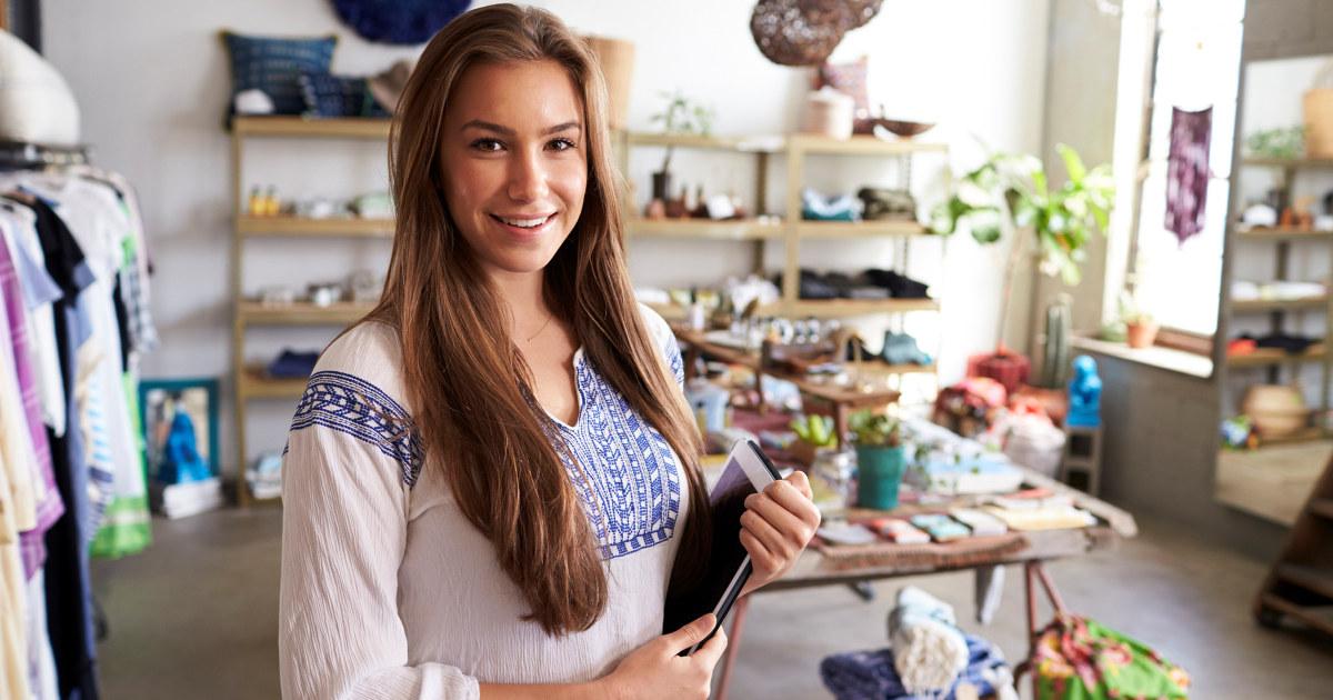 Ung kvinnelig ansatt i butikk ser i kameraet