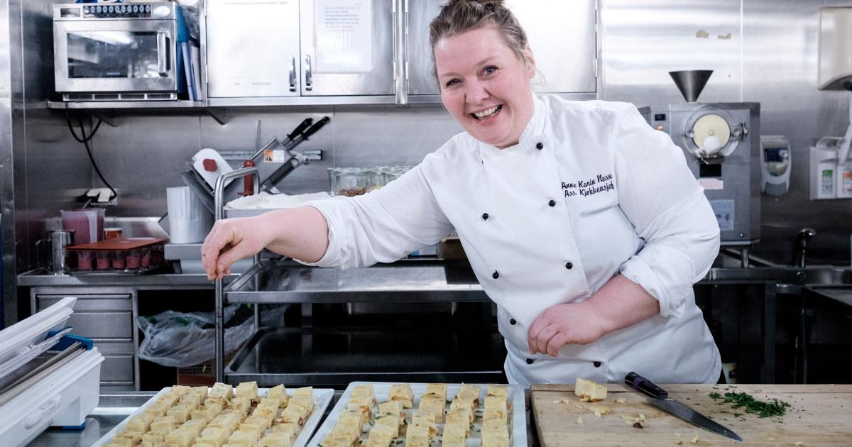 Kvinnelige kokk ser i kameraet. Ustekte bakevarer og kniv på bordet foran henne.