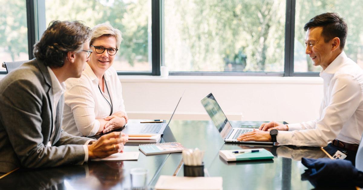 Tre kolleger snakker sammen rundt et møtebord.
