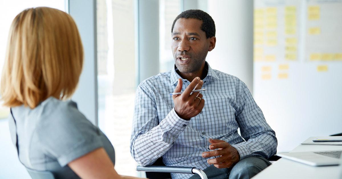 Lønnsforhandling. Kvinne og mann diskuterer over et bord utendørs.