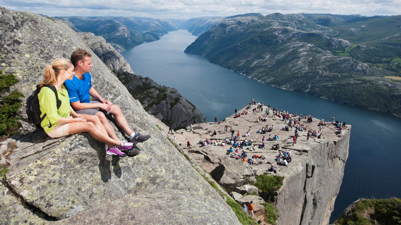 Par nyter utsikten over Lysefjorden fra fjellplatået Preikestolen i Ryfylke i Rogaland.