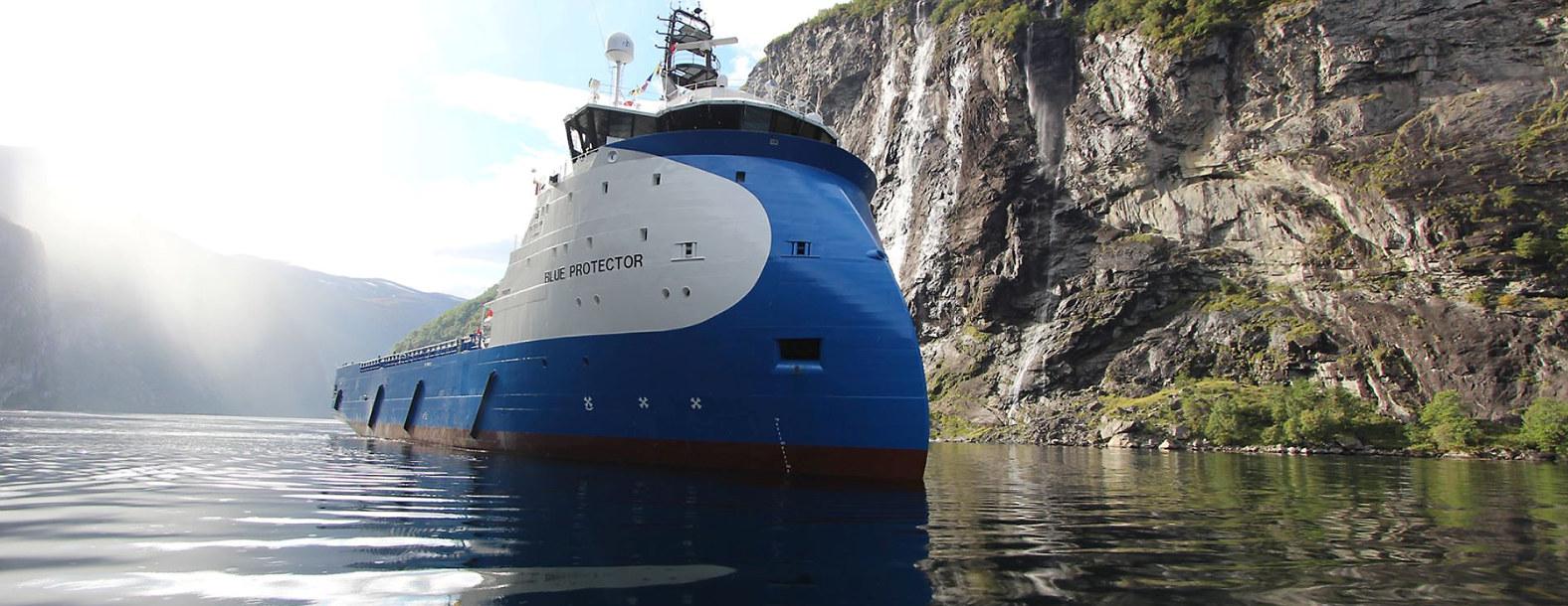 Et offshorefartøy på vei inn en fjord.
