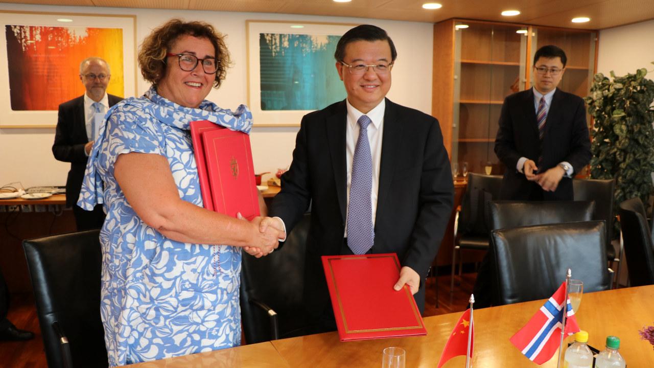 Bollestad og Yuefeng som undertegner avtalen sammen