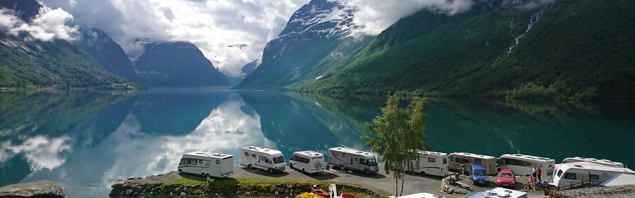 Bobiler ved sjøen på Sande Camping. Fjord og fjell i bakgrunnen.