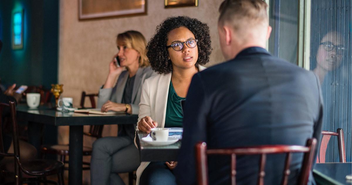 Kvinne og mann sitter på kafé og snakker sammen.