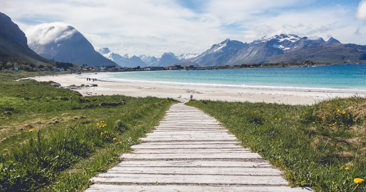 Sti av planker til norsk strand med fjell i bakgrunnen.