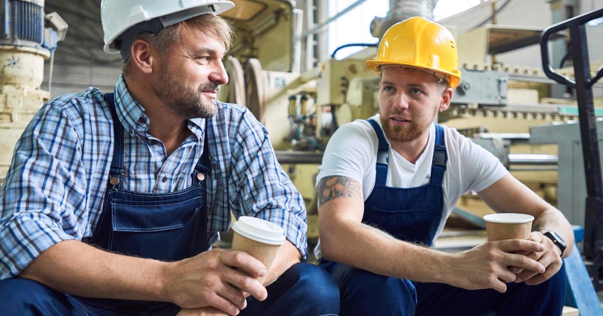 To menn med hjelm sitter og har en kaffepause.