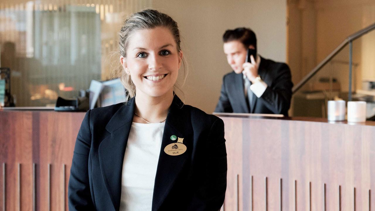 Hotellansatt, smilende jente ved resepsjonen