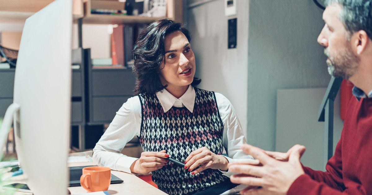 To kolleger snakker sammen foran en PC.