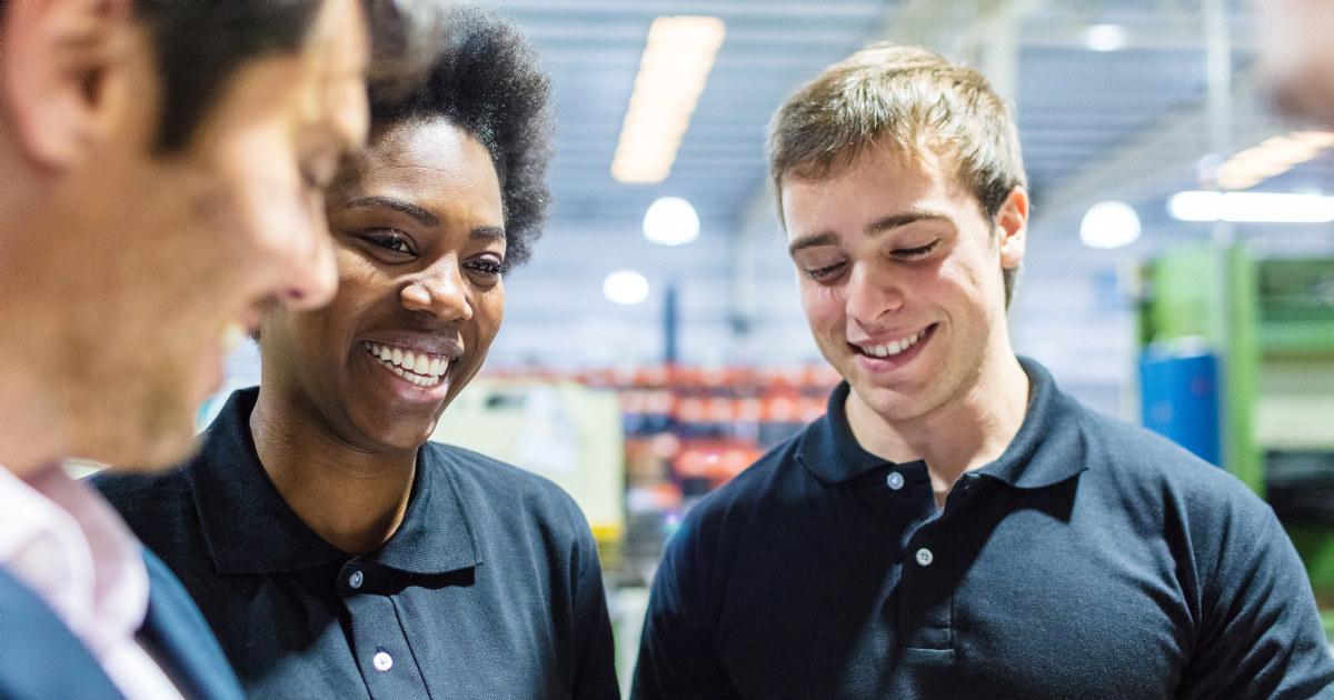 Leder snakker med to ansatte som smiler.