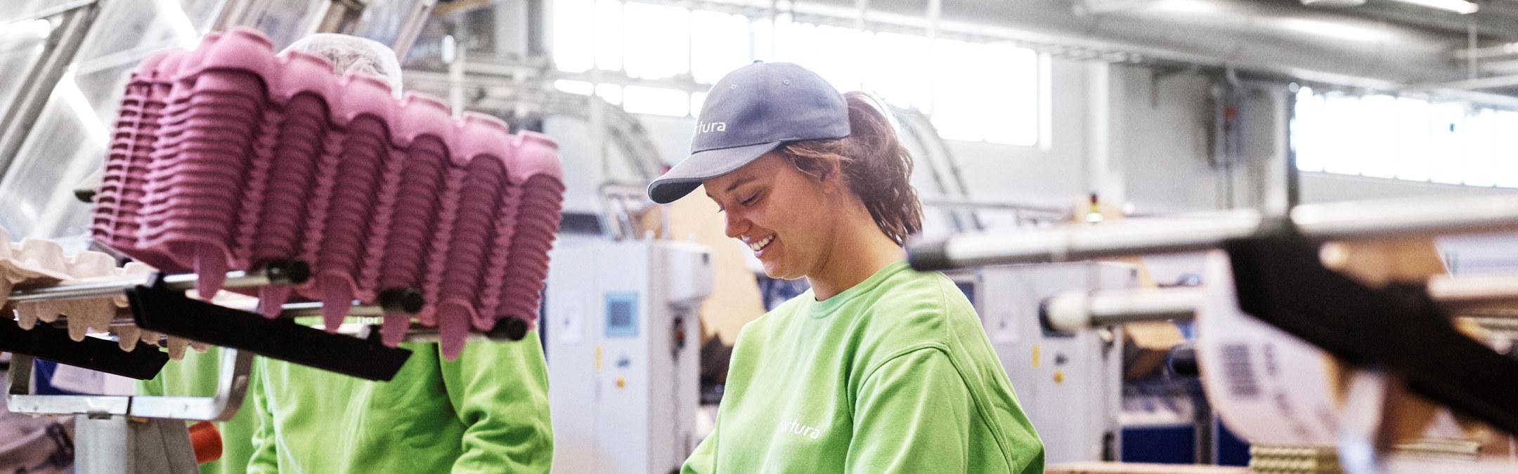 En kvinne som jobber i produksjon på et eggpakkeri